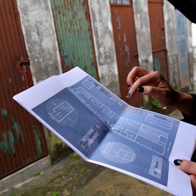 Maria mostra a planta da ilha e as alterações que prevê no projeto. Retirar as latrinas (no fundo da imagem), melhorar as condições das casas e criar espaços de convívio para várias gerações, são as prioridades