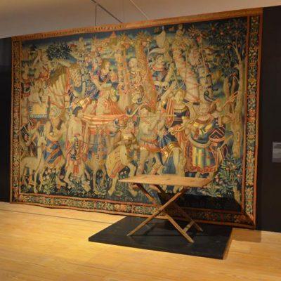 """Tapeçaria do séc. XVI, de seda e lã, representando o """"Cortejo triunfal com girafas e músicos"""". Mesa de engonços, fabricada em Ceilão no final do mesmo século, importada para a Europa"""