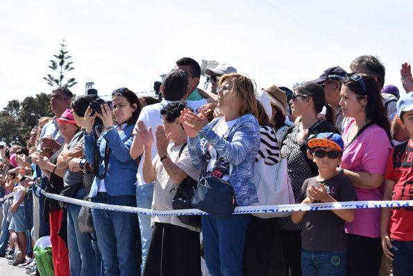 """Júlia Santos bate palmas durante o desfile das tropas. A sexagenária, de cabelo loiro e carteira azul, aplaude os militares que diz estarem """"sempre prontos a ajudar""""."""