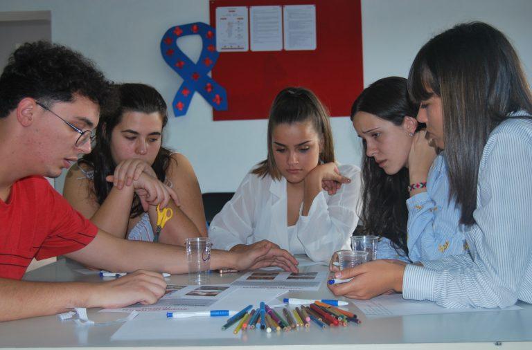 Jovens voluntários discutem liberdade e discriminação em reunião.