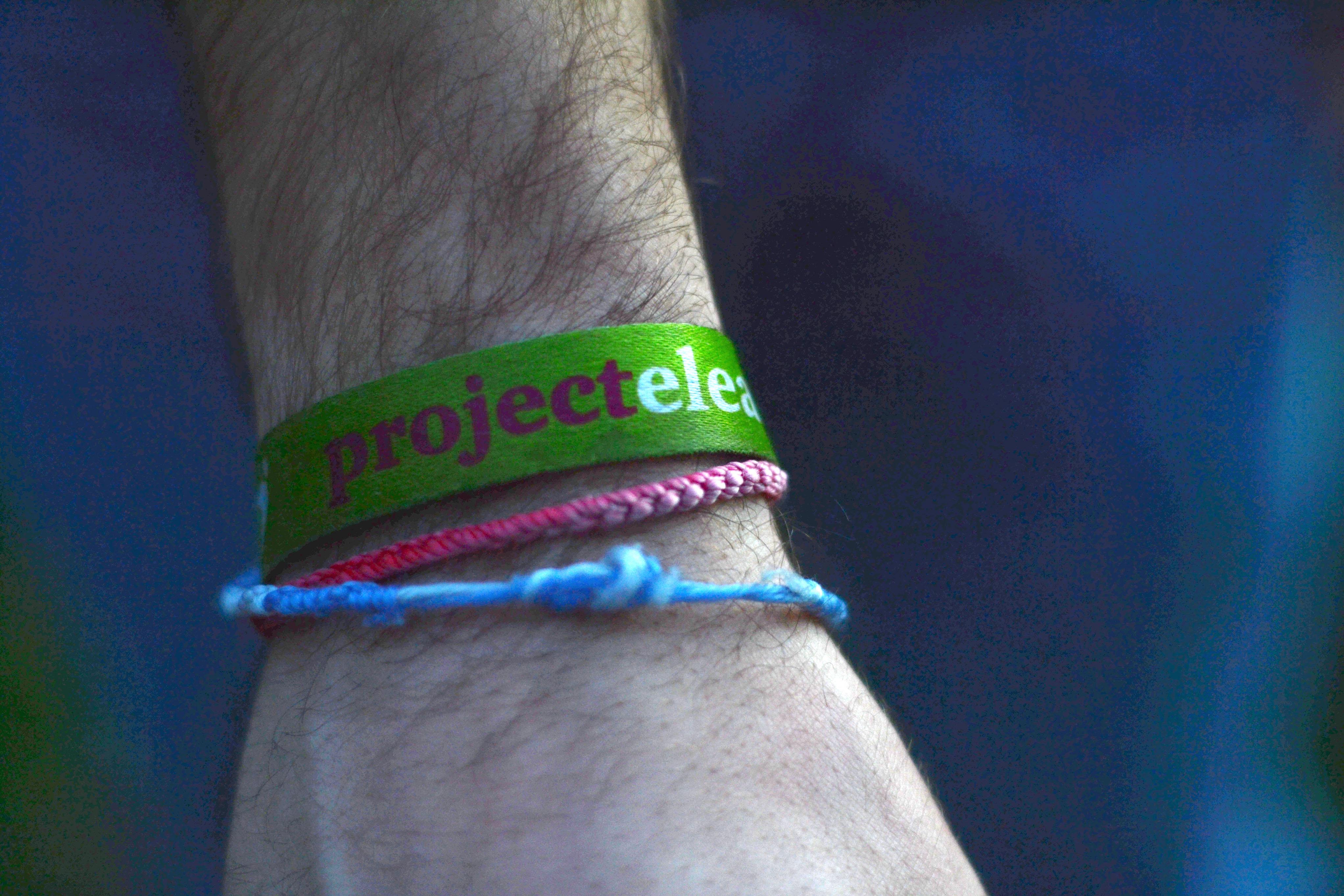 Para além da pulseira do projeto, traz duas pulseiras feitas por meninas no campo.