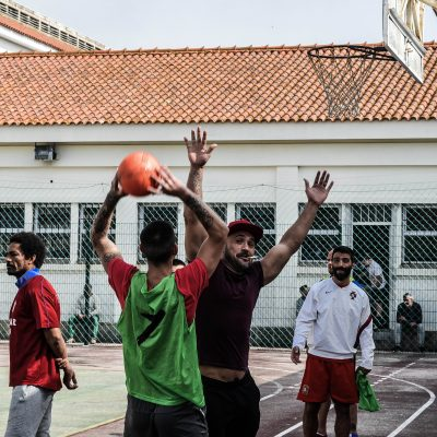 Reclusos a jogar basquetebol paralelamente ao jogo de futebol